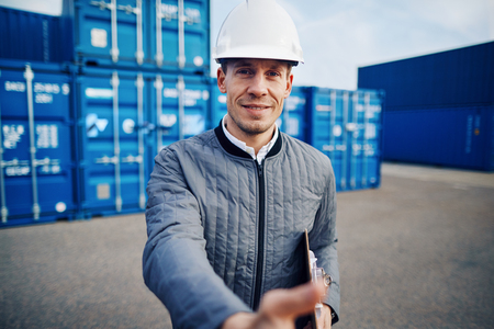 Port manager wearing a hardhat extending a handshake while standing on a large commercial shipping dock holding a clipboard Stock Photo
