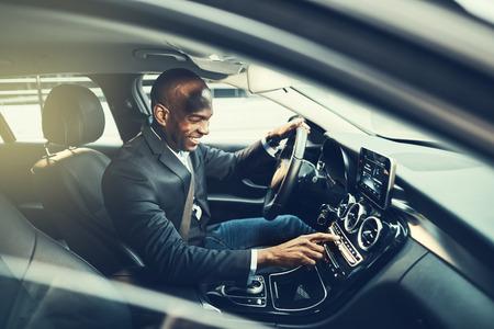 Het glimlachen van Afrikaanse zakenman veranderende posten op zijn autoradio terwijl het drijven door de stad tijdens zijn ochtend pendelt aan het werk