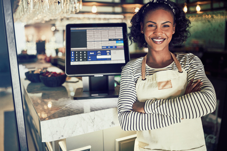 Young African waitress wearing an apron and smiling while standing by a point of sale terminal in a restaurant