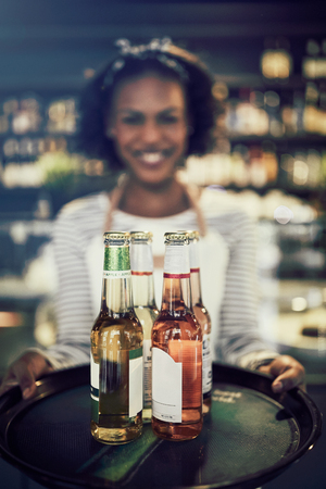 Smiling young African waitress holding a tray of colorful drinks while working in a trendy restaurant