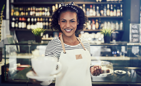 Smiling young African barista standing in a trendy cafe offering up a fresh cup of coffee Stock Photo