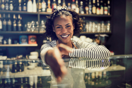 Smiling young African entrepreneur standing behind the counter of her trendy cafe extending a handshake