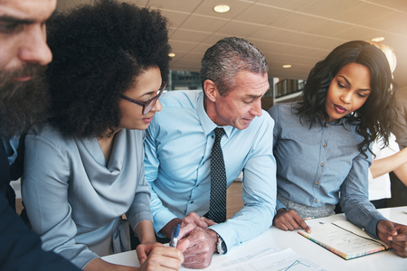 Group of diverse executives colleagues discussing documents together while having a meeting at a table in a modern office building