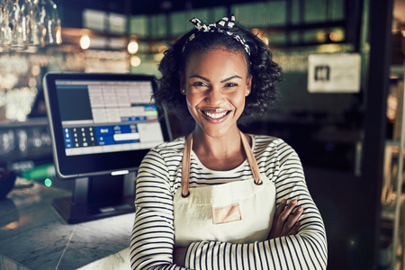 Smiling young African waitress wearing an apron and smiling while standing by a point of sale terminal in a trendy restaurant