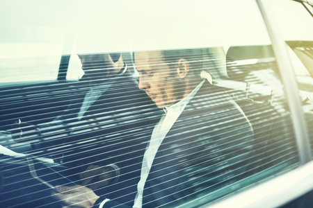 Businssman working on a digital tablet sitting with a colleague in the backseat of a car being driven through the city