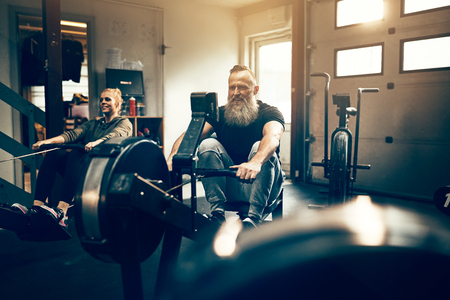 Fit mature man with a beard exercising on a rowing machine during a workout class in a gym