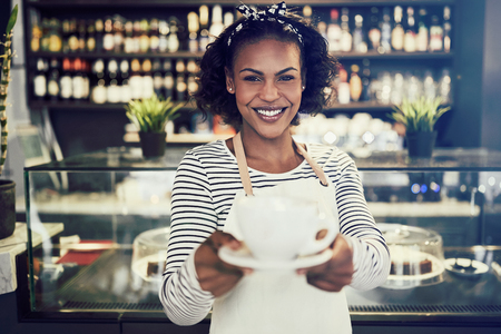 Smiling young African barista standing at the counter of a trendy cafe holding up a fresh cup of coffee