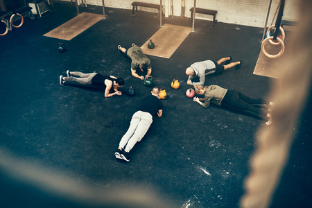 High angle of a group of fit people planking together on the floor of a gym during an exercise class Standard-Bild - 99550824
