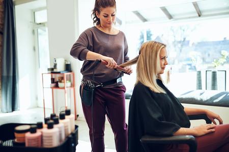 Estilista joven con una plancha en el cabello una clienta sentada en una silla mientras trabaja en su salón Foto de archivo