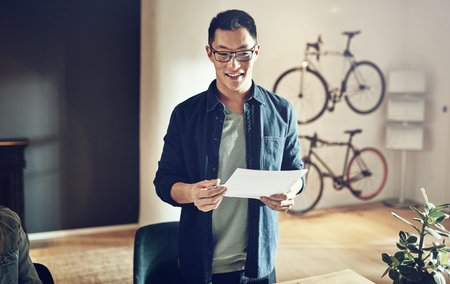 Smiling Asian man wearing glasses standing at a table discussing paperwork with colleagues in a creative modern office