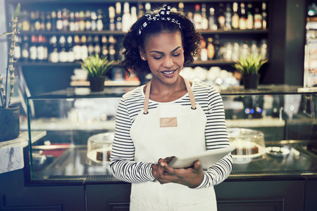 Smiling young African entrepreneur in an apron standing in front of the counter of a trendy cafe working with a digital tablet