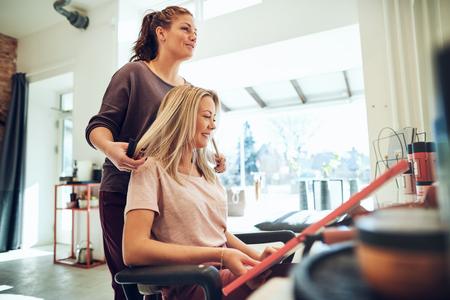サロンチェアに座っている間、彼女のヘアスタイリストと本のサンプルから新しい髪の色を選択する若いブロンドの女性