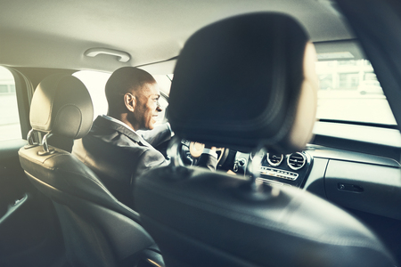 Rearview of a smiling African businessman wearing a blazer driving his car during his morning commute to work through the city Stockfoto