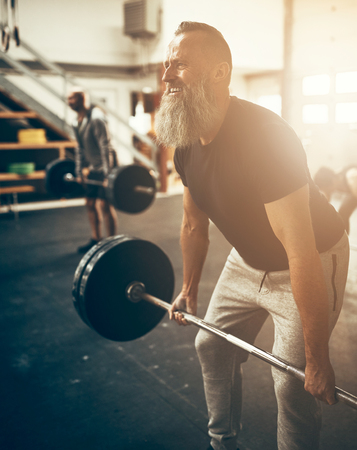 Fit mature man with a beard wearing sportswear straining to lift heavy weights during a workout session in a gym
