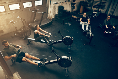 High angle of a group of people working out on rowing machines during an exercise class in a gym