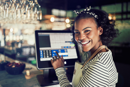 Smiling young African waitress wearing an apron using a touchscreen point of sale terminal while working in a trendy restaurant Foto de archivo