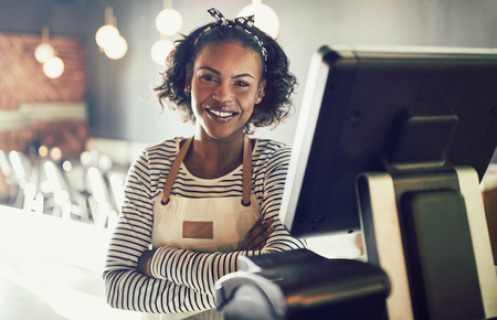 Smiling young African waitress wearing an apron standing by a point of sale terminal while working in a trendy restaurant Stock Photo