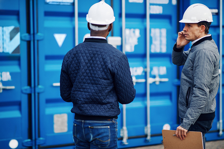 Engineer talking on a cellphone and tracking inventory with a colleague while standing by freight containers on a large commercial shipping dock