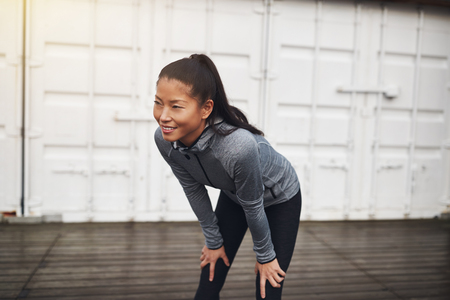 Smiling Asian woman in sportswear standing with her hands on her knees while taking a break from a jog Stock Photo