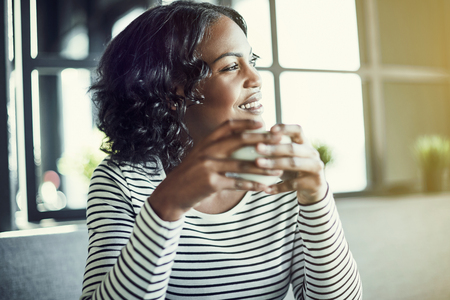 Smiling young African woman enjoying a fresh cup of coffee and looking out the window while sitting alone at a table in a cafe Stock Photo