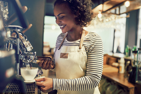 Smiling young African barista preparing a fresh cup of coffee while standing at a coffee maker in a trendy cafe Stok Fotoğraf
