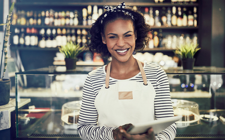 Smiling young African entrepreneur in an apron standing in front of the counter of a trendy cafe using a digital tablet