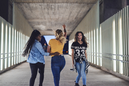 Rearview of a group of carefree young girlfriends having fun while walking together in the city at night Banco de Imagens
