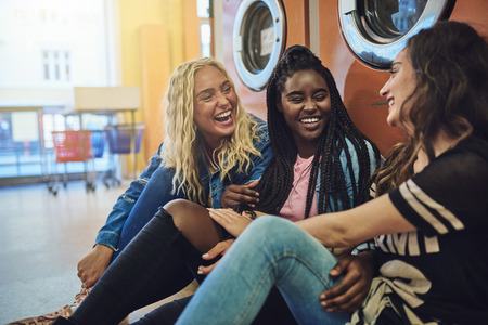 Diverse group of young girlfriends sitting together on a laundromat floor laughing and talking while doing laundry