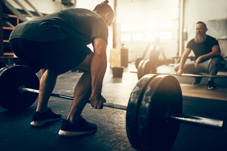 Fit young man preparing to lift heavy weights on a barbell with a partner watching during a workout session in a gym Stock Photo
