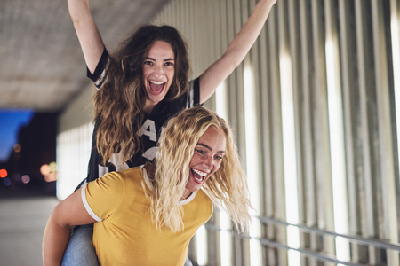 Laughing young woman being carried by her friend while enjoying a night out together in the city