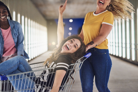 Laughing young woman being pushed in a shopping cart down a walkway in the city by two girlfriends