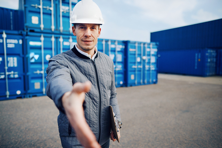 Freight foreman wearing a hardhat extending a handshake while standing on a large commercial shipping dock holding a clipboard Stock Photo