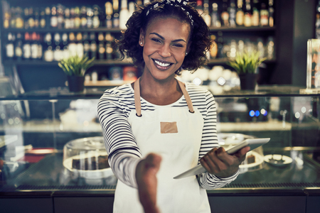 Smiling young African hostess extending a handshake while standing in a trendy cafe holding a digital tablet