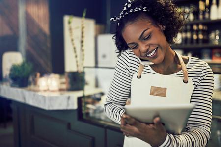 Lächelnde junge afrikanische Unternehmerin, die an der Theke ihres Cafés steht und auf einem Handy spricht und ein Tablet benutzt Standard-Bild