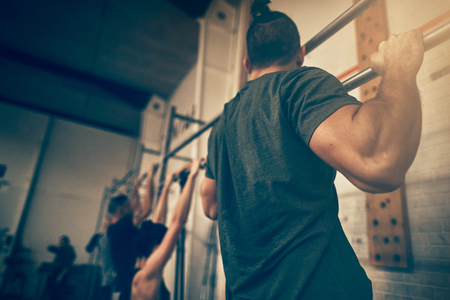 Group of fit people doing pull ups together during an exercise class at the gym