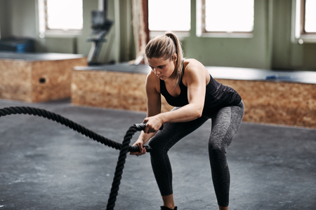 Fit young woman in sportswear working out with ropes during an exercise session at the gym Фото со стока