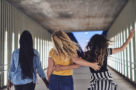 Rearview of a group of diverse young female friends walking arm in arm together down a walkway in the city at night