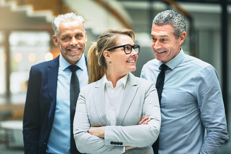 Smiling mature businesswoman talking with two male coworkers while standing together in a modern office