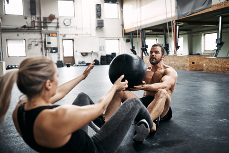 Two fit young people in sportswear sitting together on a gym floor tossing a medicine ball during an workout session