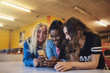 Smiling young female friends leaning on a laundromat counter using a cellphone while doing laundry together