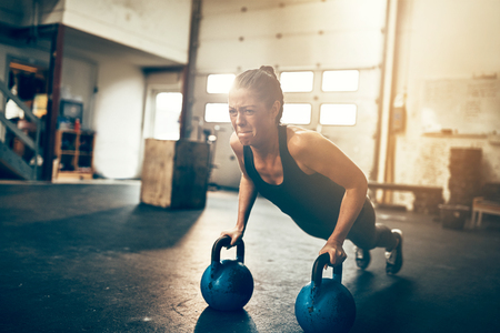 Fit young woman straining to do pushups on dumbbells while working out alone in a gym