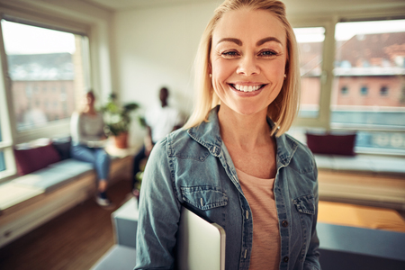 Smiling young businesswoman holding a laptop under her arm while standing in a modern office with colleagues talking in the background Reklamní fotografie - 101235565