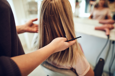Blonde woman sitting in a salon chair having her hair styled during an appointment with her hairdresser Banco de Imagens