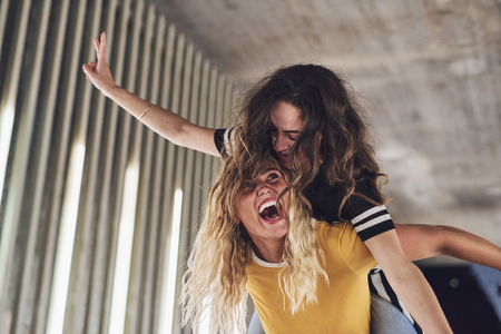 Laughing young woman carrying her friend on her shoulders while having fun together during a night out together in the city Stock Photo