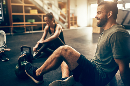 Fit people in exercise gear sitting on the floor of a gym laughing together after a workout Foto de archivo