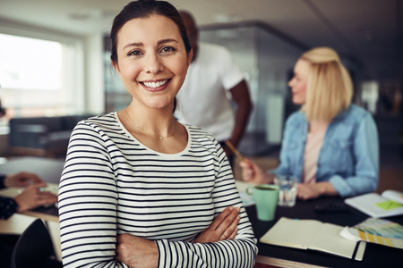 Young businesswoman smiling and sitting with her arms crossed at an office table with colleagues talking together in the background Stock Photo