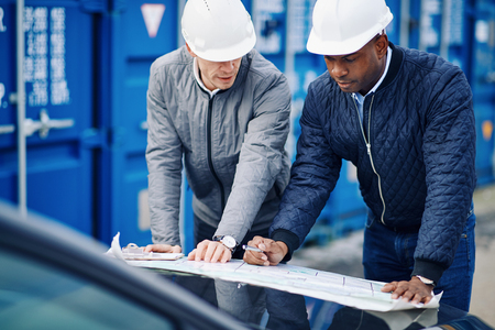 Two engineers leaning on the hood of a truck discussing building plans while standing by freight containers on a commercial dock