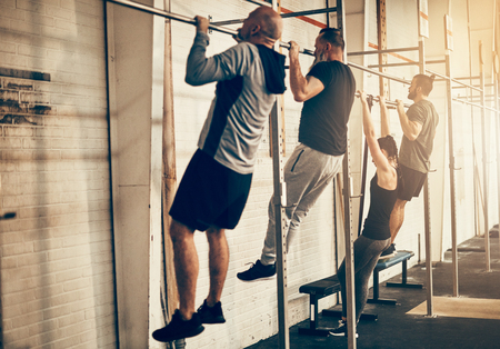 Fit group of people in sportswear doing chin ups together during an exercise class at the gym