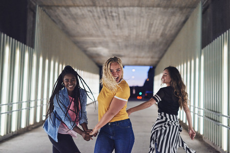 Laughing group of diverse young girlfriends having fun while walking hand in hand together along a walkway in the city at night