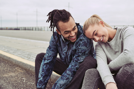 Laughing young couple sitting on a road together taking a break from a run on an overcast day Reklamní fotografie